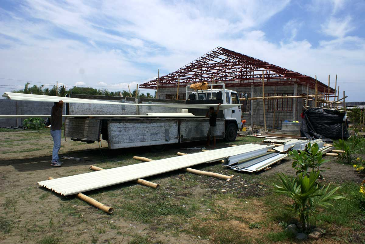 May 5, 2010 roofing arrives.  Completed roof structure in background.