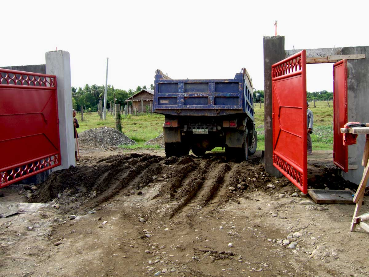 Truck leaves through new gates after leaving a load of fill.