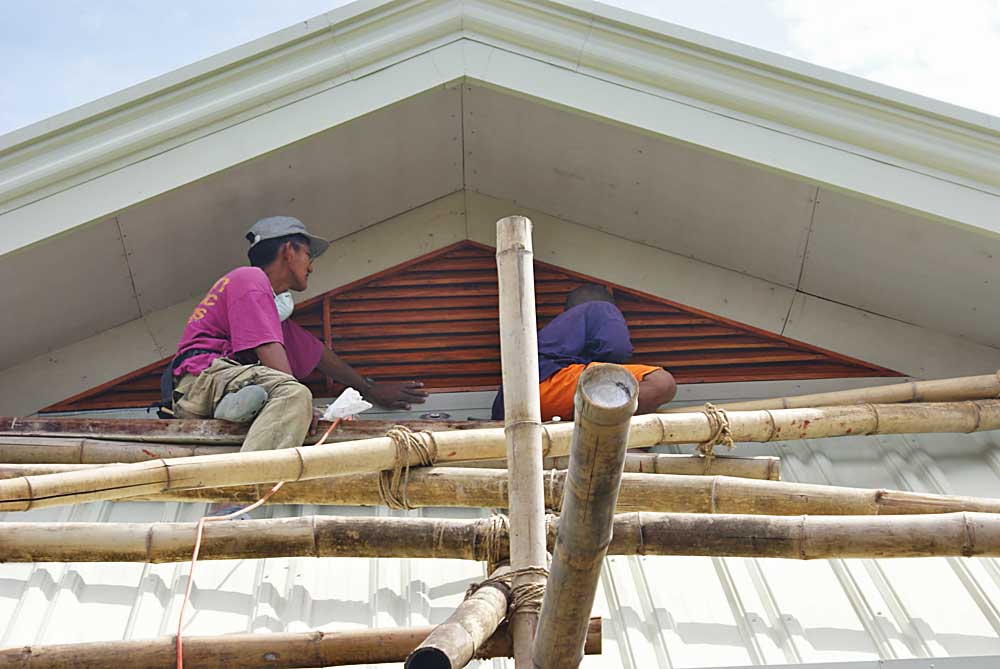 Workers install Mahogany ventilator in roof peak